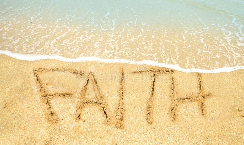 The word 'FAITH' drawn in sand on the beach