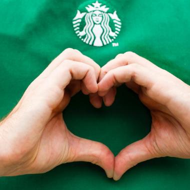 Heart hand signal from Starbucks employee wearing green apron