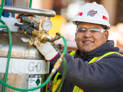 Hispanic male at a construction site wearing a hard hat and protective eyeglasses