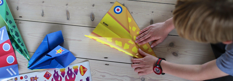 child making paper plane