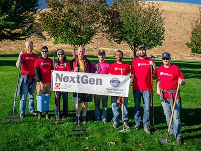 """A group of men and women at a garden, with gardening tools and matching red T-shirts, carrying a """"Nextgen"""" banner"""
