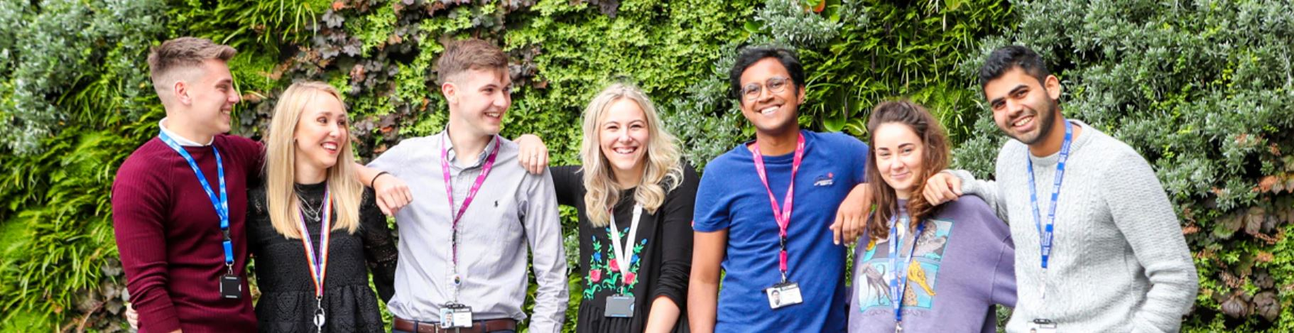 Image of 7 young apprentices standing leaning on each others shoulders smiling at the camera