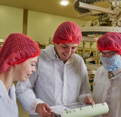 3 Graduates looking at a clipboard wearing red hair nets and white over coats
