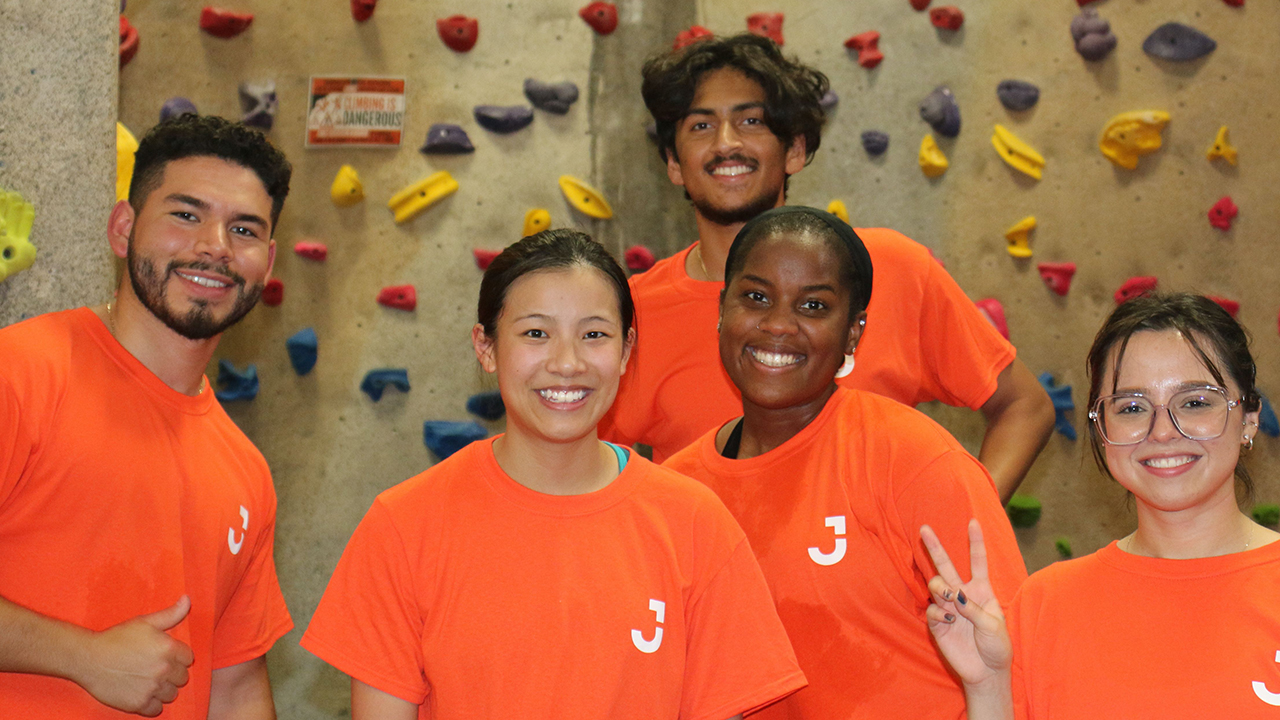 5 interns in orange t-shirt smiling at the camera they are stood infront of a climbing wall