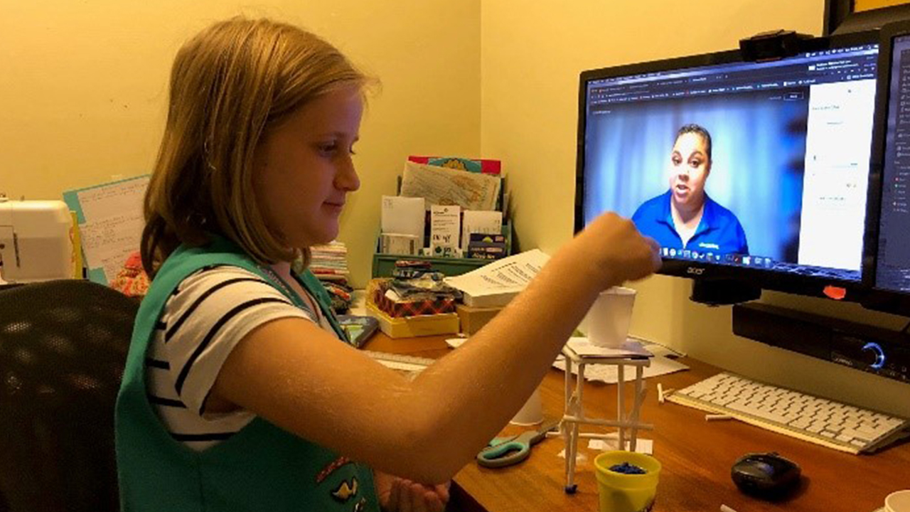 Young girls on a zoom call with a someone from Jacob's Women's Network doing an small engineering experiment