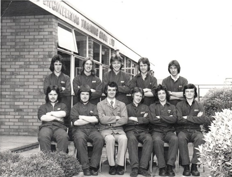 Black and white photo of 11 males standing and sitting