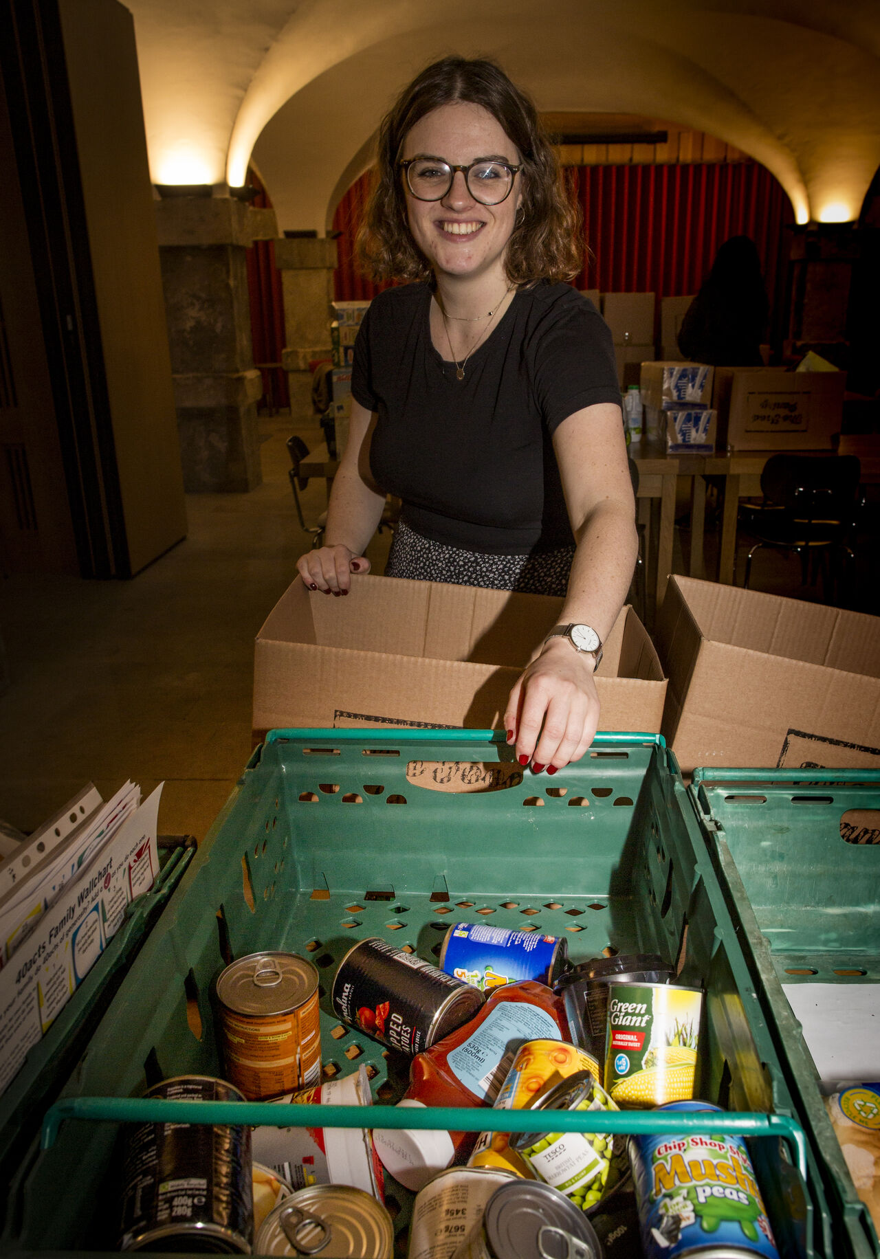 Image of a smiling female with a tray of cans and tins at the food bank