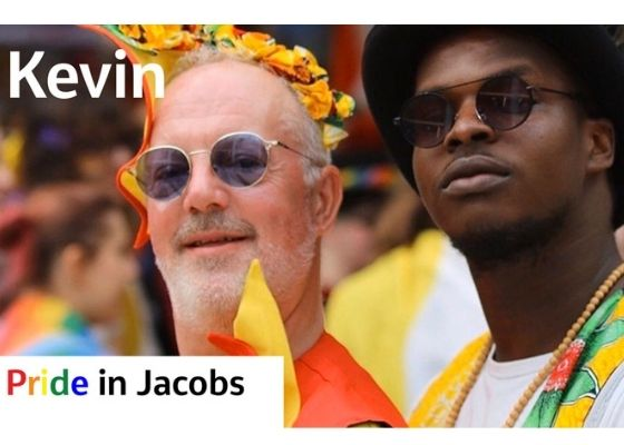 Image a white man and a black man at Pride wearing sunglasses
