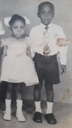 black and white photo of 2 small black children, a little boy and a little girl