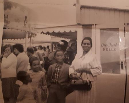 Old picture of a smiling black family outside a bakery