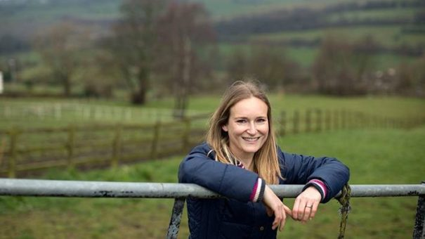 Barclays employee, Bev Clarkson leaning against a fence in a field