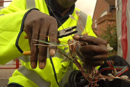 Image of a black male empliyee of openreach working on some cables