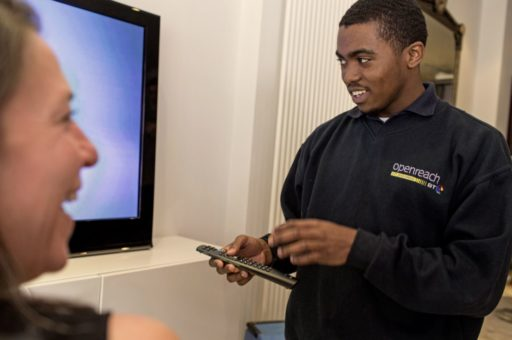 Image of a black male openreach employee setting up a TV
