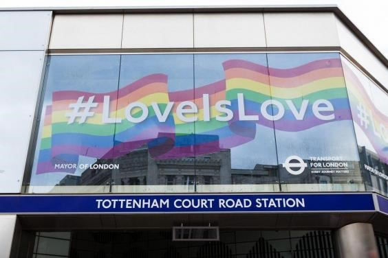 Pride flag with slogan #LoveIsLove across the top of Tottenham Court Road Station