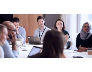 Image of BEIS group of employees in a meeting setting.