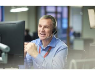 A man talking on a headset whilst looking at his computer