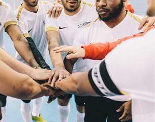Diverse football players linking hands.