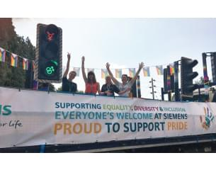 Group of Siemens employees holding a banner that reads 'Supporting equality, diversity and inclusions. Proud to support pride'.