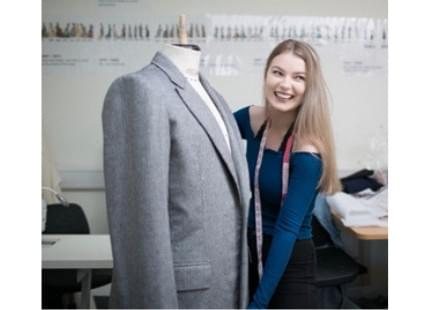 Bethan, an intern, standing next to a costume project for the set.