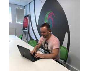 Tattooed man working on a laptop