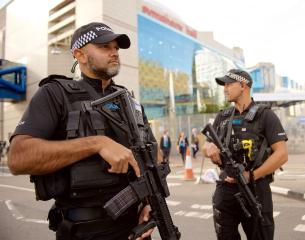 2 armed male officers on patrol.