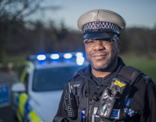 Black male traffic officer on patrol standing in front of his vehicle.