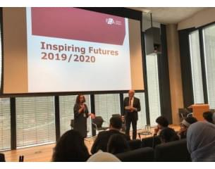 A presentation to a group of diverse people with a projections reading 'inspiring futures 2019/2020'.
