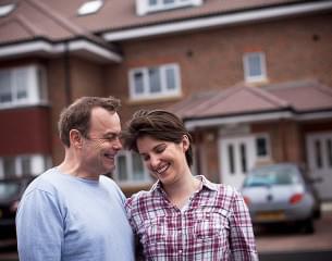 White couple outside their house.