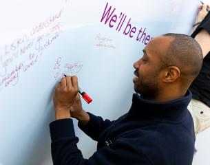 BAME member of staff writing on ideas board.