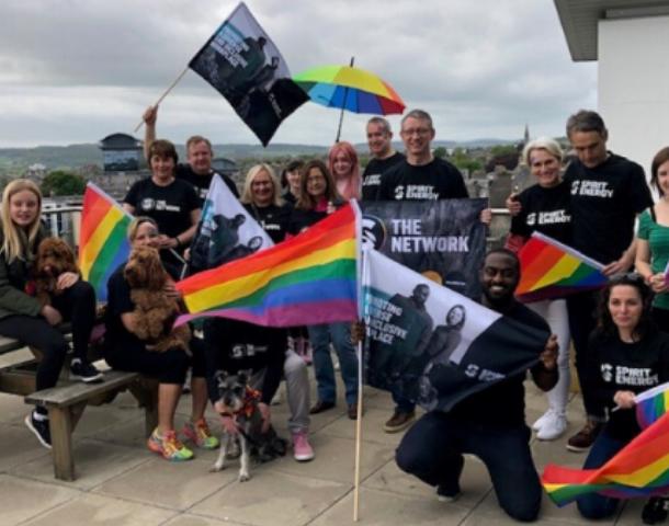 Spirit Energy staff holding rainbow flag.