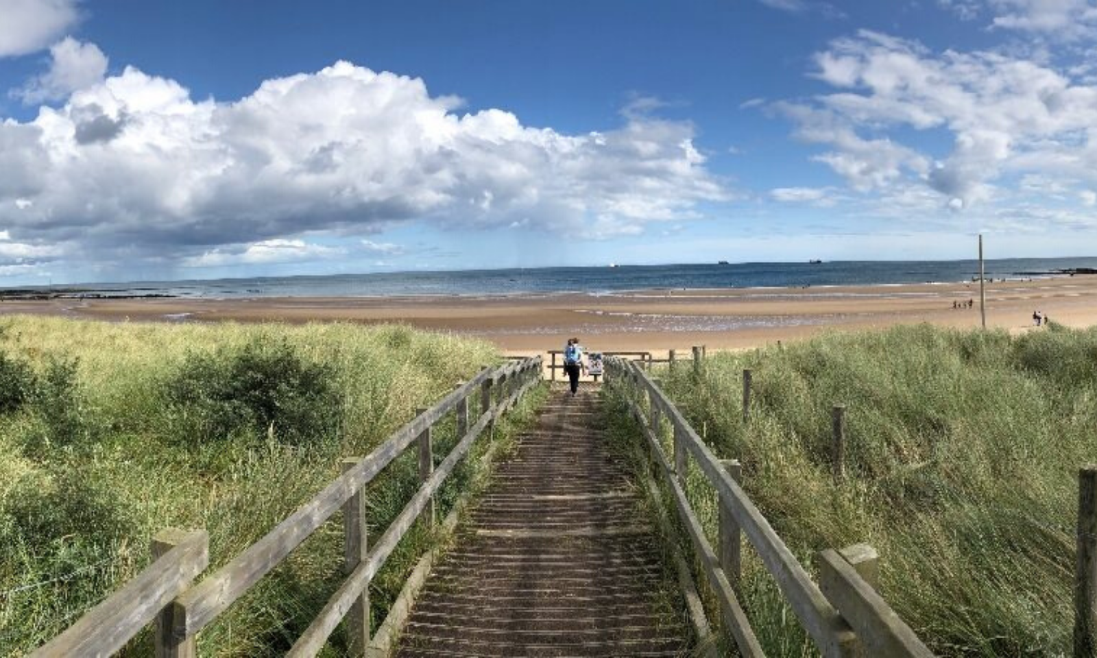 Two people walking on a boardwalk towards a beach front.