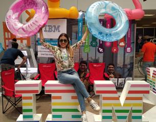 IBM member of staff at London PRIDE 2019, sitting on top  of large IBM letters.