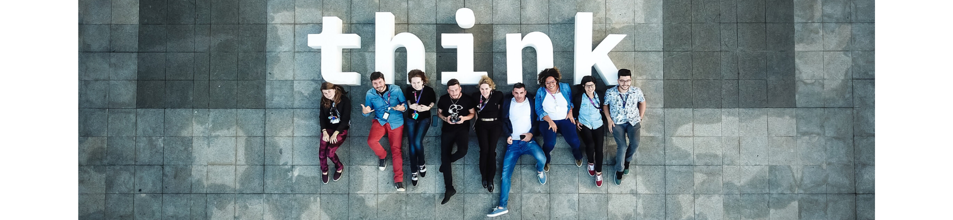 9 young IBM staff laying on the floor looking up with the work 'think' underneath them.