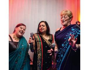 two white women and one asian women in tradional indian sari