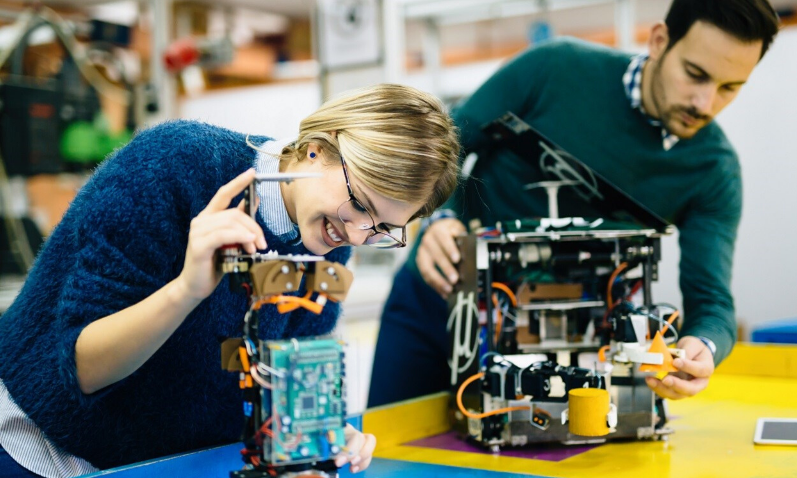 Women and a man working on  circuit boards.