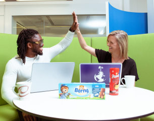 black man and white women high fiving with a box of barny cakes