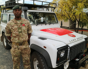 Male DIO staff standing in front of Land Rover in Nepal.