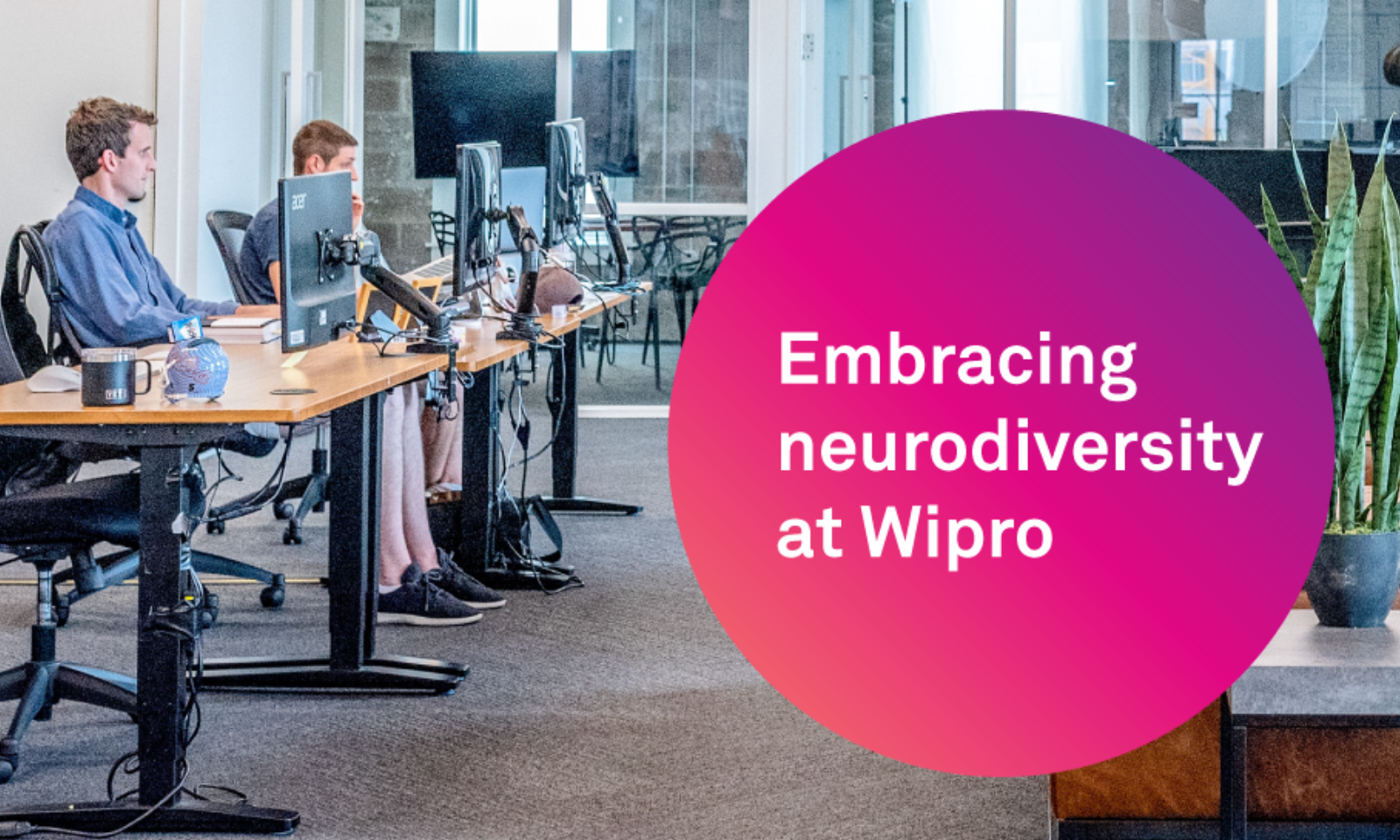 Embracing neurodiversity at Wipro  - Image of 2 males working at terminals within an office setting.