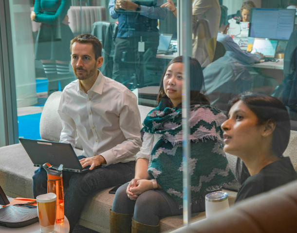 1 male, and 2 female Avanade employees in a meeting setting, listening and taking notes.