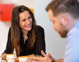 A female Avanade employee talking with 2 male colleagues over hot beverages.