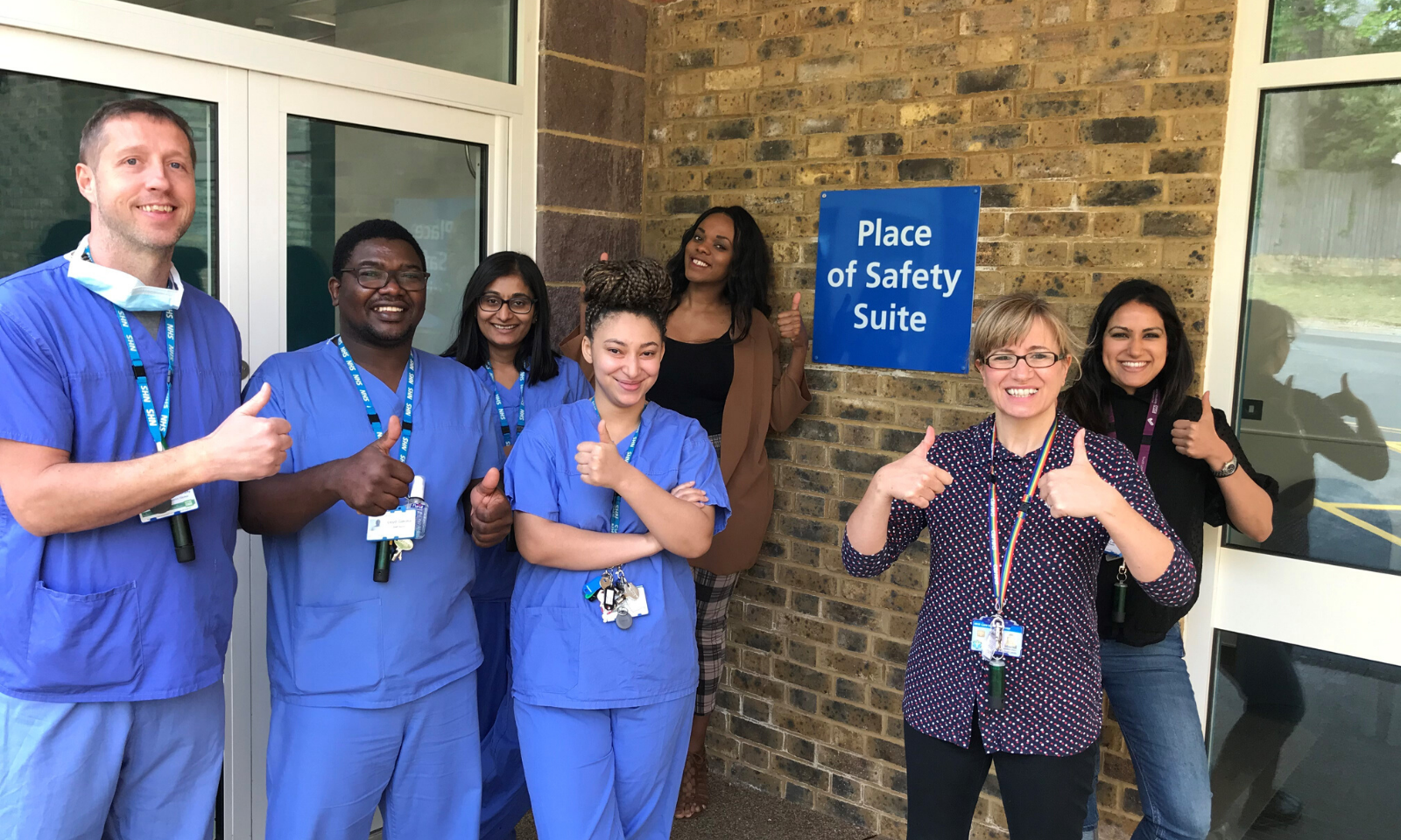 NHS staff standing outside  Place of Safety Suite holding their thumbs up.