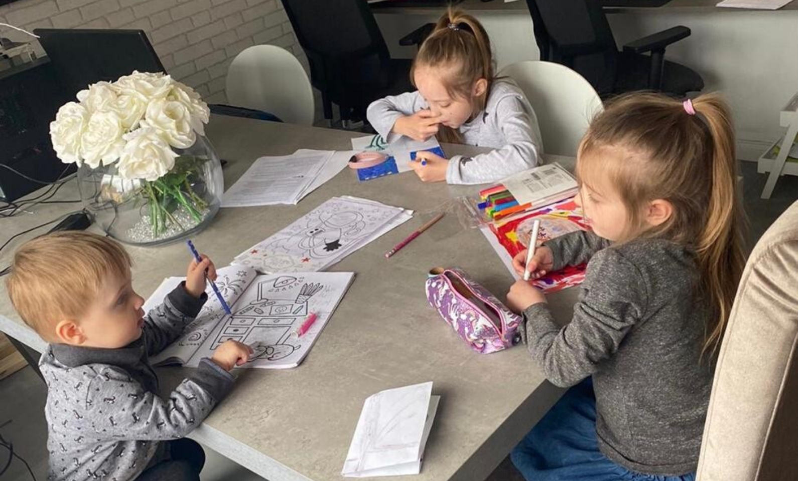 3 children drawing around a table
