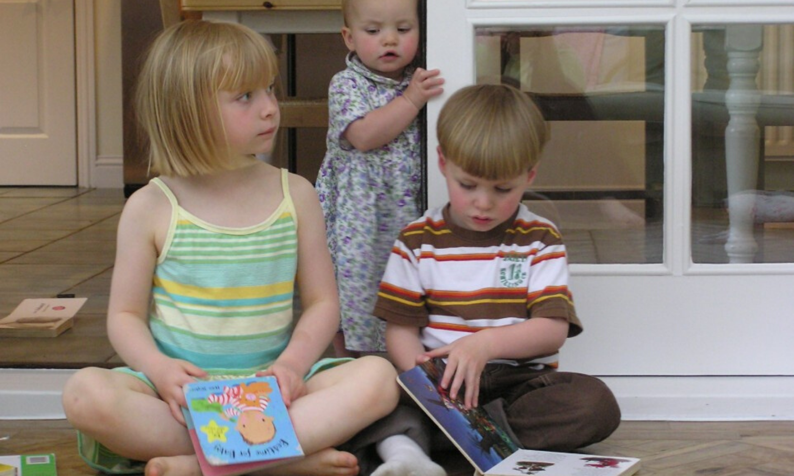 3 young children reading at home
