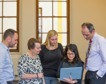DCMS staff huddled around a laptop