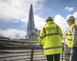 2 male colt employees in high vis coats and hard hats, across from the Shard, separated by the river Thames