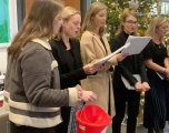 Female employees carol singing for charitable causes