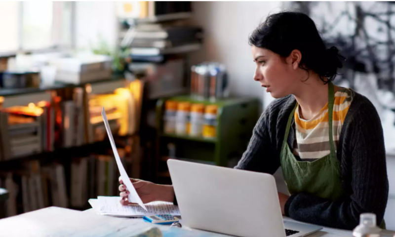 Female working from home visibly pained by reading a letter