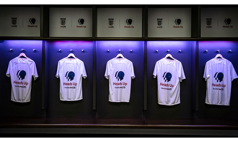 Football tops hanging in England dressing room with Heads Up on back