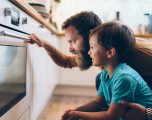 Father and infant son kneeling in front of an oven watching food cook.