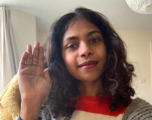 Female Intapp staff member striking the Choose To Challenge pose, with yhand high to show their commitment.